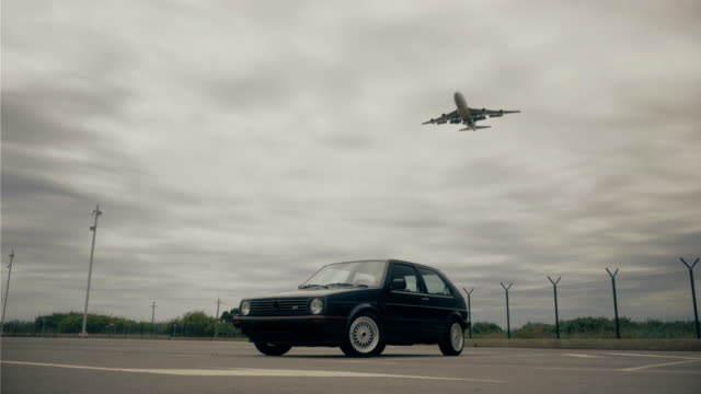 Old car and airplane passing by during landing