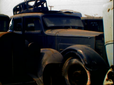 Old dirty Firestone whitewall tire zoom out to old abandoned 1930s Packard automobile resigned to junkyard / auto junkyard and scrap heap detritus...