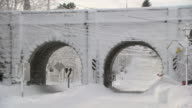 Old double-arch stone railroad bridge plastered with snow and deep drifts