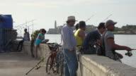 Old Havana, Cuba: Cuban people fishing in 'El Malecon' at dusk.