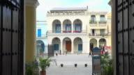 Old Havana, Cuba: 'Plaza Vieja' establishing shot framed in old wooden colonial door architecture.