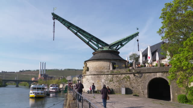 Old historic harbour crane (quay crane) in Würzburg at the Main river. People walking.