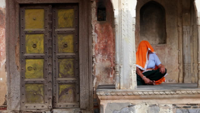 A old lady, with covered head, sits by an old Haveli, a private mansion, with a decorated doorway in a village in Rajasthan in India
