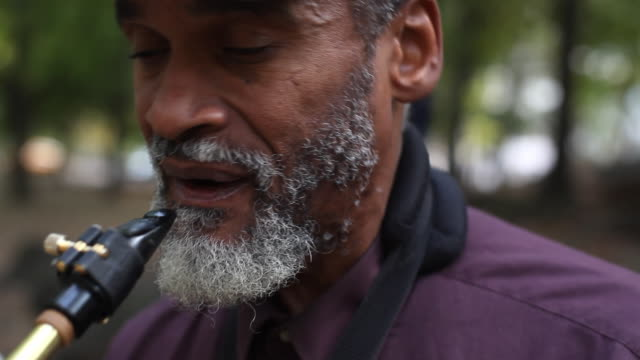 Old man plays saxophone in urban park, stares into camera, and wipes sweat from brow