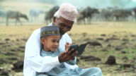 Old muslim man with little boy playing mobile phone.