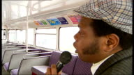 Old Routemaster bus tour Tour guide Alaba Sofuyi speaking SOT / back view bus driver driving / TRACKING SHOT past Walthamstow Stadium