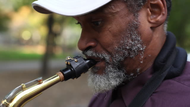 Old street musician plays saxophone in New York City park