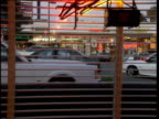 Old style white stretched limo pulls up outside American diner view through window and blinds