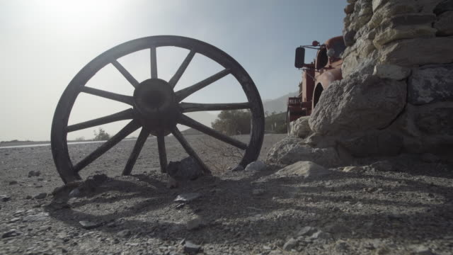 Old wagon wheel stuck in the sand