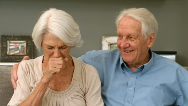 Old woman coughing next to her husband