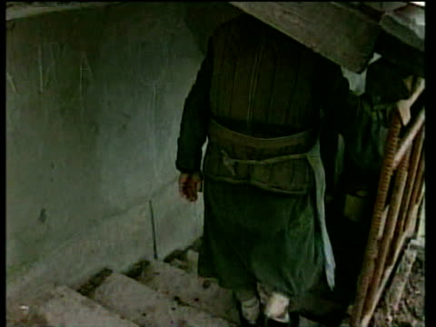 Old woman enters bomb shelter cellar used to hide from Russian forces during bombing shows rainwater they collect to drink Grozny 18 Feb 00