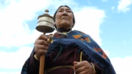 Old woman holding hand prayer wheel