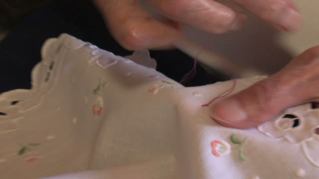 Old woman patiently embroidering