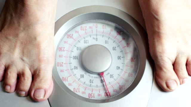 Old woman stepping on weight scale