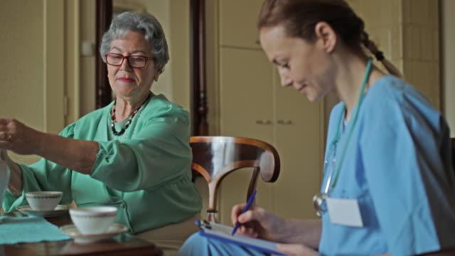 Oude vrouw naar huis verzorger te praten tijdens de middag thee thuis.