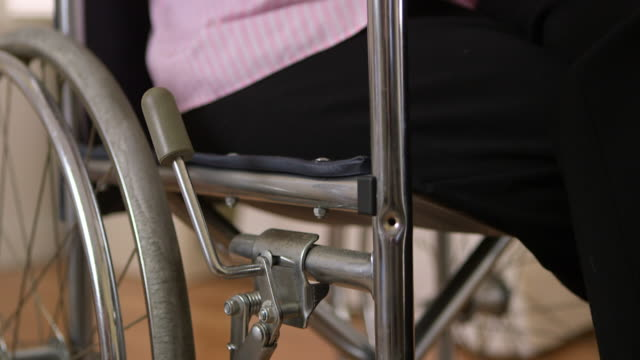 Old woman using smartphone in wheelchair