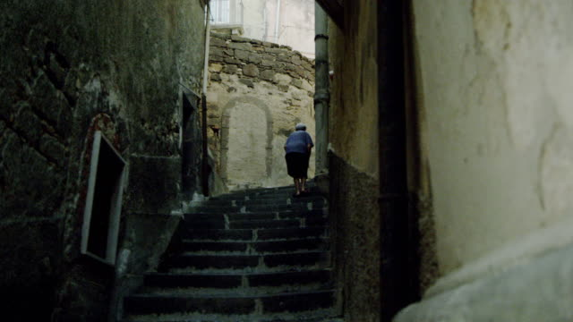 Old woman walks up stairs
