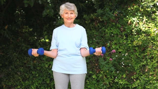 MS Old woman working on muscles with dumbbells in garden / Cape Town, Western Cape, South Africa