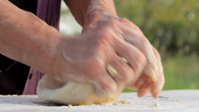 Old wrinkled farmers hands making bread