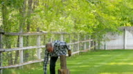 Older Caucasian man carrying ax in yard answering cell phone