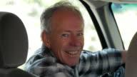 Older Caucasian man smiling in car