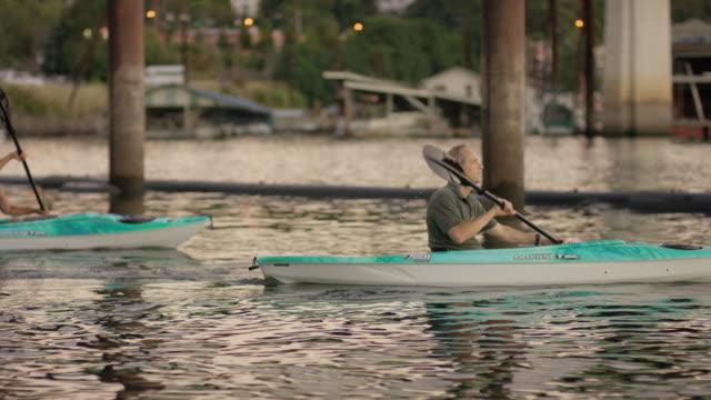 Older mature couple kayaking together during summer
