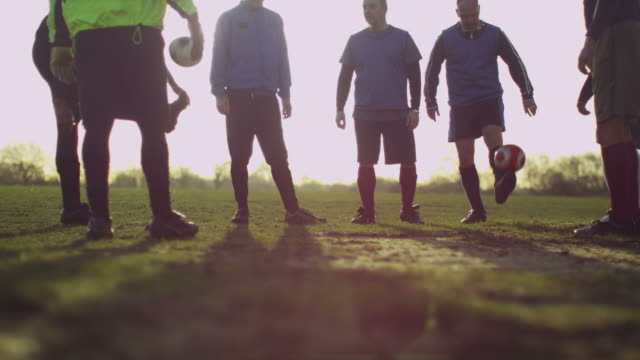 older men keeping fit playing football in nature