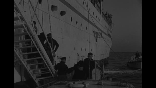 Older people descend gangplank of ship / VS Orthodox Jews assisted into motor launch / people inside ship at windows / VS people clustered at...