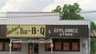 MS Older single story commercial retail store. Sign reads Goudeans BAR-B-Q & Appliance Store