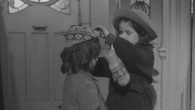 1947 MS Older sister helping a younger sister get coat and hat on before leaving house / United Kingdom