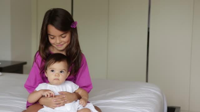 MS Older sister hugging baby sister on bed