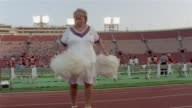 1985 WS Older woman doing cheerleader routine at USFL game/ USA