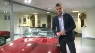 Oldest Jaguar dealership R A Creamer to close Kensington INT Reporter to camera Michael Quinn showing royal warrant badges to reporter SOT **Quinn...