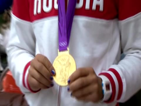 Olympic athlete from the Russian squad kisses her gold medal at London airport