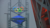 WS Olympic rings on tower with detail of Bird's Nest Olympic Stadium in foreground / Beijing, China