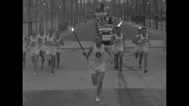 Olympic rings superimposed over runner carrying Olympic torch / runner hands off Olympic flame by touching his torch to that of relay runner / MS...