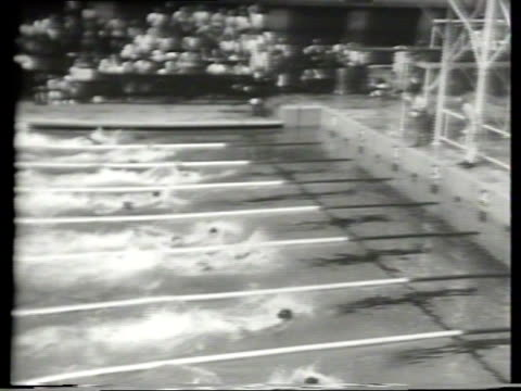 Olympic swimming competitors on the starting blocks dive in for 100M freestyle / USA swimmer Wally Reese sets a new Olympic record / US takes first...
