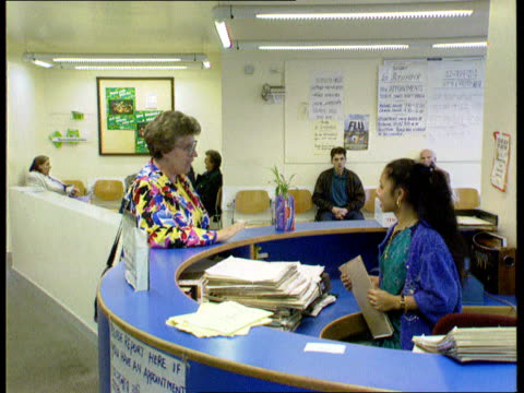 Ombudsman report criticises NHS ENGLAND MS People in hospital waiting room as one speaks to receptionist