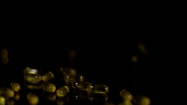 HD SLOW MOTION: Omega Capsules Falling On Glass