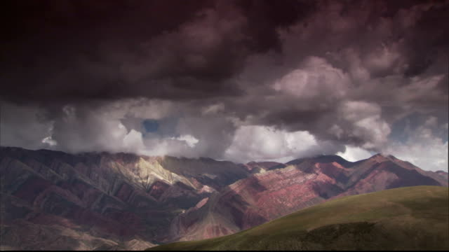 Ominous clouds churn over mountains. Available in HD.