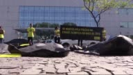 On a large sidewalk in front of the 2016 Rio Olympic Committee building some 15 Amnesty International activists on Wednesday demonstrate by spreading...