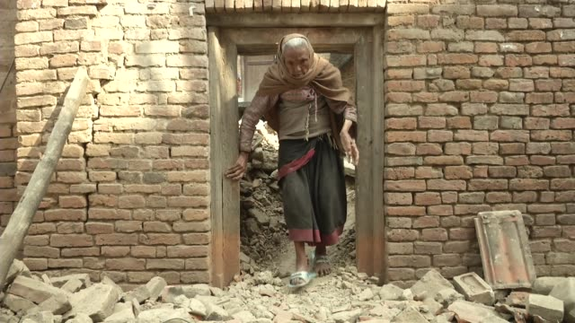 On old woman walk out of her destroyed home in Khokana / A major earthquake hit Kathmandu midday on Saturday April 25th and was followed by multiple...
