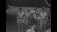 On tarmac of airfield next to plane Gen Douglas MacArthur Supreme Commander of Southwest Pacific Area pins Distinguished Service Medal on General...