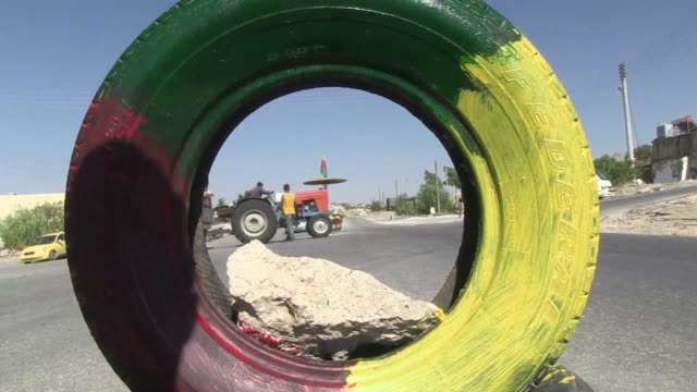 On the main road to the northern Syrian town of Afrin armed men stand beneath green red and yellow Kurdish flags welcoming truckloads of their...