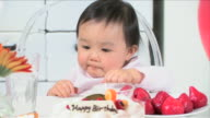 One baby is eating a strawberry and enjoying party