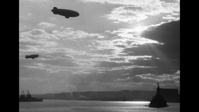 MS one blimp flies over two large Navy ships on Hudson River other smaller ships around dark clouds / MS two blimps fly over two large Navy ships sun...