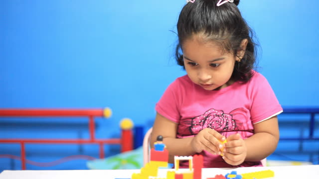 One cheerful Indian little girl playing with blocks