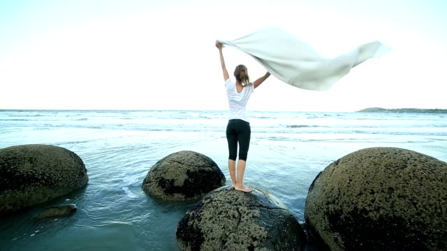 One female stands on boulder, holds blanket in the air