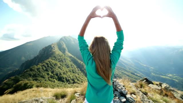 Een vrouw waardoor hart vorm boven op de berg