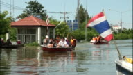One woman waves from a boat of rescued Thailanders crammed into a small boat is it crosses floodwaters in Ayutthaya Province